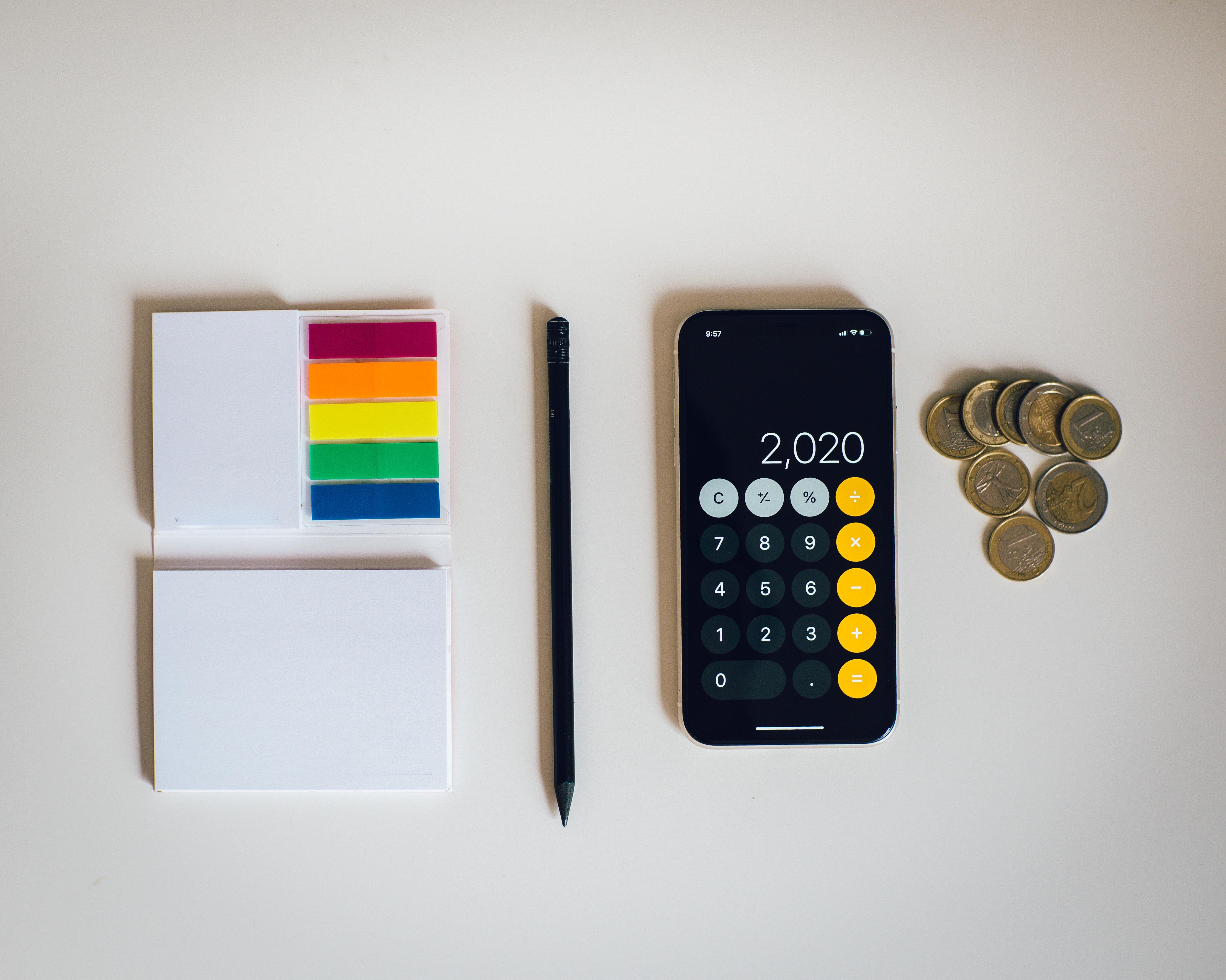 Калькулятор в телефоне и монеты для подсчета налогов